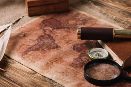 world map near telescope and magnifying glass on wooden surface