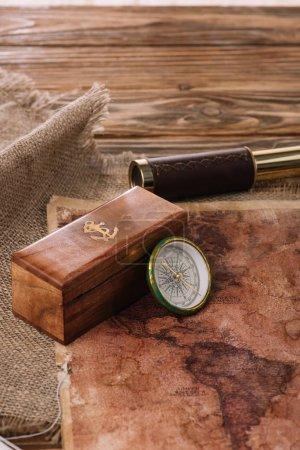 Photo pour Boîte avec logo ancre près boussole sur table en bois avec sac et carte du monde - image libre de droit