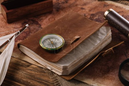 brown leather notebook with compass on wooden surface with world map