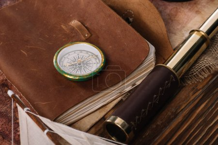 compass on copy book with leather cover near telescope on wooden surface