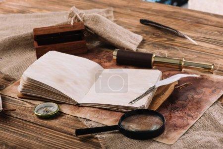 Photo pour Livre ouvert de copie avec des pages blanches près du télescope, de la boussole et de la loupe sur la table en bois avec la carte de Hesse et du monde - image libre de droit