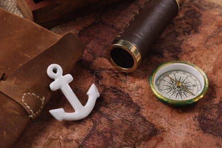 Photo pour Ancre blanche près du livre de copie en cuir, de la boussole et du télescope sur la carte de vieux monde - image libre de droit