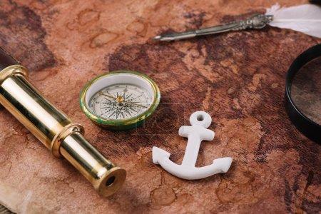 Photo pour Boussole, ancre blanche, plume et télescope sur la carte du monde - image libre de droit