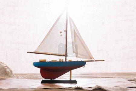 Photo pour Navire décoratif avec voile blanche sur la surface avec Hessian - image libre de droit