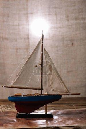 Photo pour Navire décoratif avec la voile blanche sur la surface en bois - image libre de droit