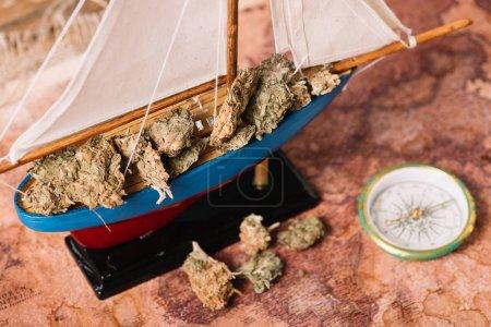 Photo pour Navire décoratif avec des morceaux secs de plante près de la boussole sur la carte de vieux monde - image libre de droit