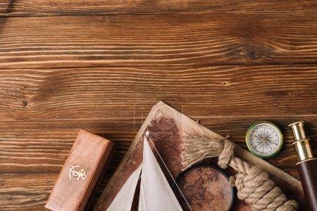 Photo pour Vue du dessus de la carte, loupe, boussole, câble de corde, télescope et boîte avec logo sur la surface en bois - image libre de droit