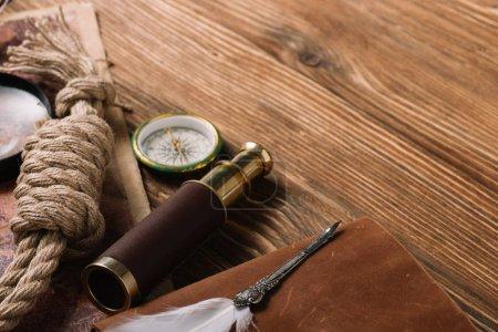Photo pour Câble de corde, plume, boussole et télescope sur la surface en bois - image libre de droit