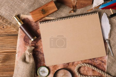 top view on copy book near nib, telescope, compass on wooden surface with map and hessian