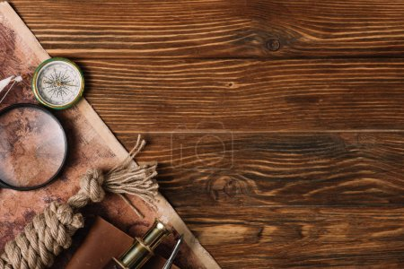 Photo pour Top view of map, magnifying glass, compass and rope cable on wooden surface - image libre de droit