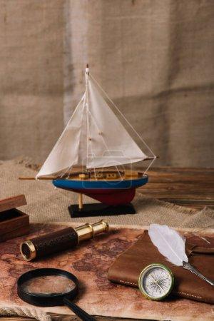 Foto de Barco en miniatura, telescopio, lupa, libro de cuero, brújula y plumón en el viejo mapa del mundo y hessian - Imagen libre de derechos