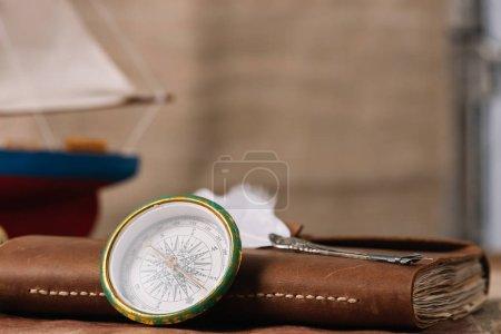 Photo pour Boussole près de carnet en cuir brun avec plume - image libre de droit