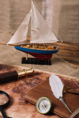 Foto de Barco en miniatura, telescopio, lupa, libro de copia de cuero y plumón en el viejo mapa del mundo y hessian - Imagen libre de derechos