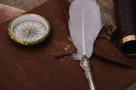 Photo pour Plume et boussole sur cuir copie livre sur hessian - image libre de droit