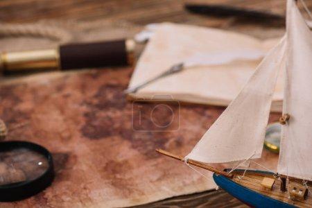 Photo pour Bateau artisanal près de la carte de vieux monde avec la loupe et le télescope - image libre de droit