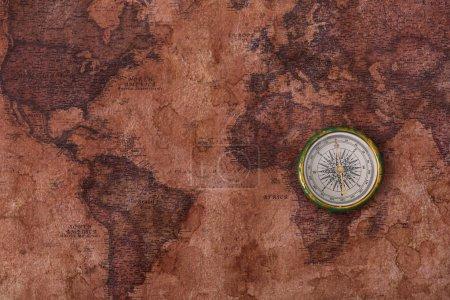 Photo pour Vue du dessus de la boussole sur l'ancienne carte du monde - image libre de droit