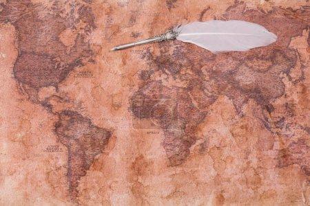вид сверху на перо с белым пером на карте древнего мира