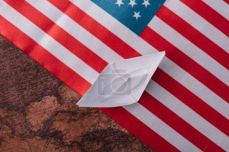 Photo pour Vue supérieure du bateau de papier blanc sur la carte antique de monde avec le drapeau national américain - image libre de droit