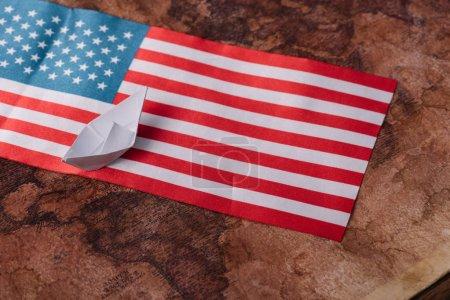 Photo pour Bateau de papier blanc sur la carte antique de monde avec le drapeau national américain - image libre de droit