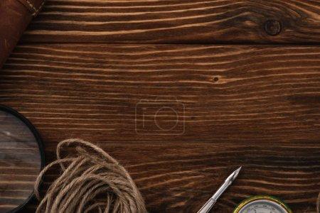 Foto de Vista superior en el cordel cerca de la lupa, la punta y la brújula en la superficie de madera con el espacio de copia - Imagen libre de derechos