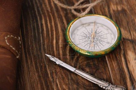 Photo pour Fermer vers le haut la vue de la boussole près de la plume sur la surface en bois brune - image libre de droit