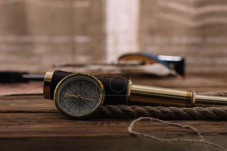 Photo pour Boussole près du télescope et du câble de corde sur la table en bois brun - image libre de droit