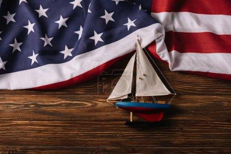 Photo pour Vue supérieure du bateau artisanal en cuir sur la surface en bois avec le drapeau national américain - image libre de droit