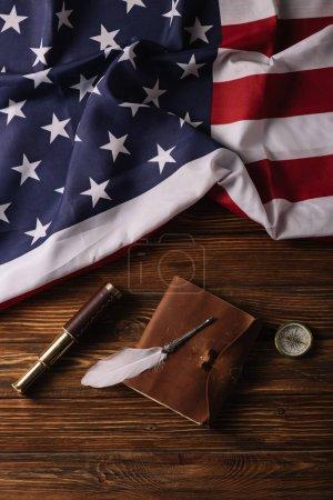 Photo pour Vue supérieure du cahier en cuir, de la plume, du télescope et de la boussole sur la surface en bois avec le drapeau national américain - image libre de droit