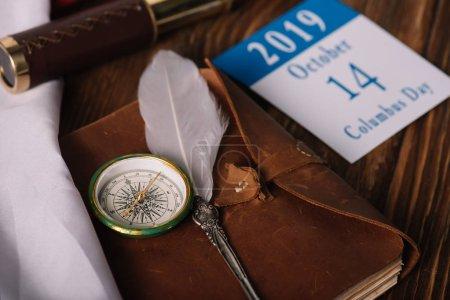 Photo pour Calendrier avec Octobre 14 date près de carnet en cuir avec plume et boussole sur la surface en bois - image libre de droit