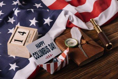 Photo pour Carte avec l'inscription heureuse de jour de Columbus près du calendrier, bateau de papier, plume, boussole, télescope et cahier sur la surface en bois avec le drapeau national américain - image libre de droit