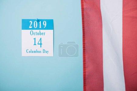 Photo pour Calendrier papier avec l'inscription de jour de Columbus près d'une partie du drapeau national américain sur le fond bleu - image libre de droit