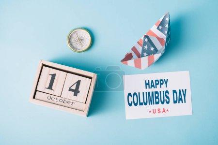 Photo pour Vue supérieure du calendrier avec le bateau de papier du 14 octobre près du bateau de papier avec le modèle de drapeau américain, la boussole et la carte avec l'inscription heureuse de jour de Columbus sur le fond bleu - image libre de droit