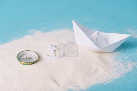 Photo pour Sable avec bateau de papier, boussole et ancre sur le fond bleu - image libre de droit