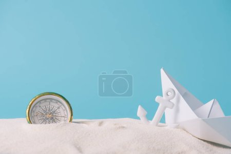 Photo pour Sable blanc avec bateau en papier, boussole et ancre isolée sur le bleu - image libre de droit