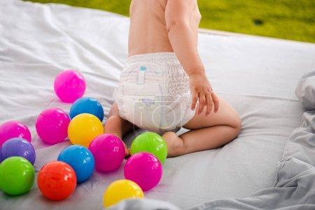 Foto de Cropped view of cute baby in diaper sitting on bed among colored balls - Imagen libre de derechos