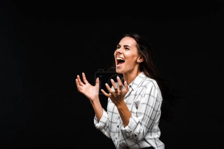 Photo for Emotional woman screaming and gesturing isolated on black - Royalty Free Image