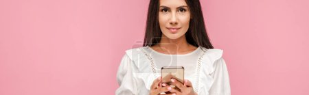 Photo for Panoramic shot of beautiful girl in white dress holding smartphone isolated on pink - Royalty Free Image