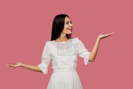 fröhliche Frau im weißen Kleid gestikuliert vereinzelt auf rosa