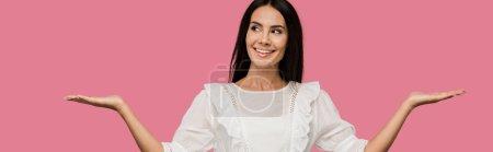 Panoramaaufnahme einer fröhlichen Frau im weißen Kleid, die isoliert auf rosa gestikuliert