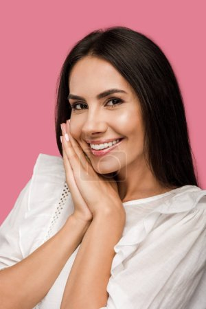 happy woman looking at camera and smiling isolated on pink