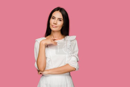 Photo pour Femme attirante dans la position de robe et regardant l'appareil-photo d'isolement sur le rose - image libre de droit