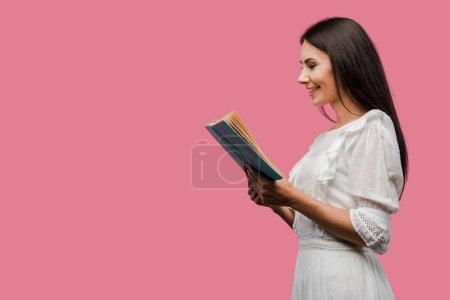 fröhliche Frau im Kleid liest Buch isoliert auf rosa
