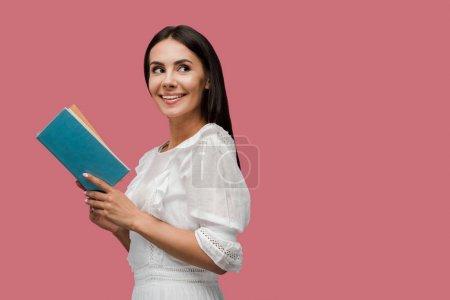 Photo pour Heureuse jeune femme en robe tenant livre isolé sur rose - image libre de droit