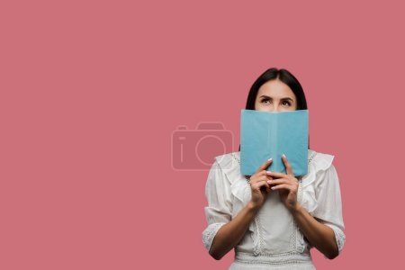Photo for Young woman in dress covering face with book isolated on pink - Royalty Free Image