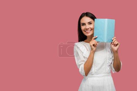 Photo pour Joyeuse jeune femme en robe tenant livre bleu isolé sur rose - image libre de droit