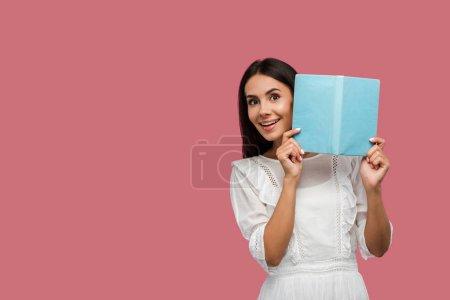 Photo pour Positive jeune femme en robe tenant livre bleu isolé sur rose - image libre de droit
