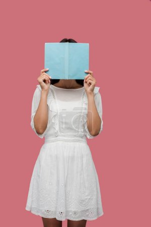 Photo for Young woman in dress covering face while reading blue book isolated on pink - Royalty Free Image