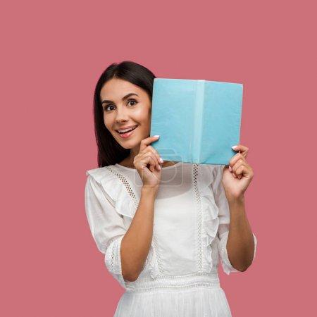 Photo pour Femme heureuse en robe blanche tenant livre bleu isolé sur rose - image libre de droit