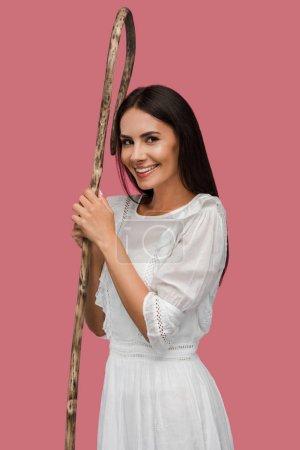 fille gaie tenant canne en bois isolé sur rose