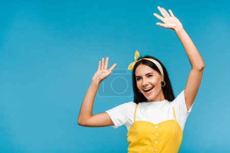 Photo for Happy young woman in headband gesturing isolated on blue - Royalty Free Image